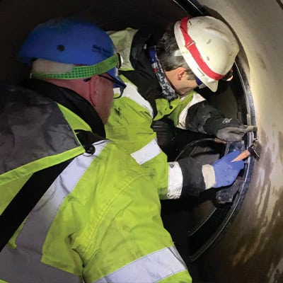 Two HydraTech technicians inserting a wedge into the restraining bands to hold the HydraTite Seal in Place