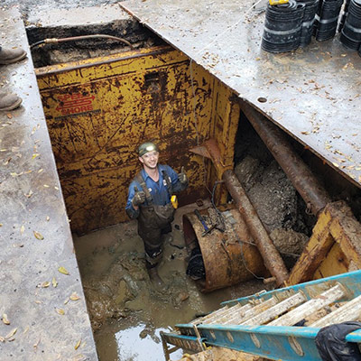 A Field Services Technician down near the entrance of the pipe